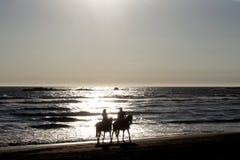 pares a cavalo para a caminhada romântica na praia imagens de stock