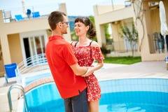 Pares cerca de la piscina Imagen de archivo libre de regalías