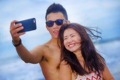 Pares chineses asiáticos felizes e bonitos novos que tomam a foto do selfie com o sorriso da câmera do telefone celular alegre Fotografia de Stock