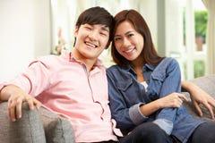 Pares chineses novos que relaxam no sofá em casa Imagem de Stock Royalty Free