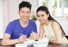 Pares chineses novos que sentam-se em casa comendo a refeição Fotos de Stock