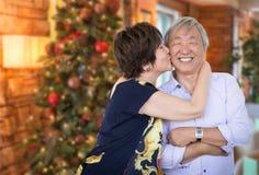 Pares chineses superiores felizes que beijam na frente de Cristo decorado foto de stock