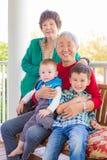 Pares chinos adultos mayores que se sientan con su raza mixta Grandc Fotos de archivo libres de regalías