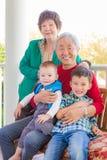 Pares chinos adultos mayores que se sientan con su raza mixta Grandc Foto de archivo libre de regalías