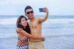 pares chinos asiáticos hermosos que toman la foto del selfie con la sonrisa de la cámara del teléfono móvil alegre divirtiéndose  Fotos de archivo