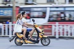 Pares chinos en una bici eléctrica o Fotos de archivo
