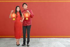 Pares chinos jovenes con el vestido tradicional que sostiene las linternas rojas Fotografía de archivo libre de regalías