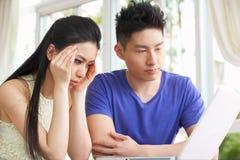 Pares chinos jovenes preocupantes usando la computadora portátil Imágenes de archivo libres de regalías