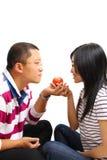 Pares chinos jovenes que comparten una manzana Imagenes de archivo