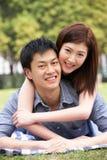 Pares chinos jovenes que se relajan en parque junto Foto de archivo
