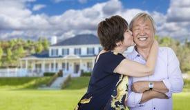 Pares chinos mayores cariñosos delante de la casa hermosa Imagen de archivo libre de regalías