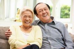 Pares chinos mayores que se relajan en el sofá en el país Imagen de archivo libre de regalías