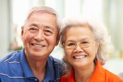 Pares chinos mayores que se relajan en el sofá en el país Imagenes de archivo