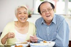 Pares chinos mayores que se sientan en el país comiendo la comida Imagen de archivo libre de regalías