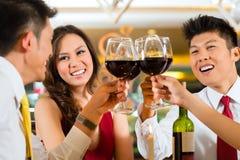 Pares chinos que tuestan con el vino en restaurante Fotos de archivo