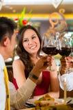 Pares chinos que tuestan con el vino en restaurante Fotografía de archivo