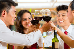 Pares chinos que tuestan con el vino en restaurante Imagenes de archivo