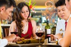 Pares chinos que tuestan con el vino en restaurante foto de archivo libre de regalías