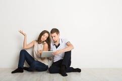 Pares chocados usando el ordenador portátil, sentándose en piso Imagen de archivo libre de regalías