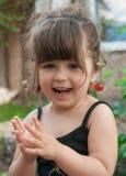 Pares colgantes de la niña pequeña de cerezas en su oído Imagen de archivo libre de regalías