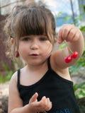 Pares colgantes de la niña pequeña de cerezas en su oído Fotos de archivo