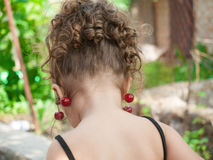 Pares colgantes de la niña pequeña de cerezas en su oído Fotografía de archivo libre de regalías