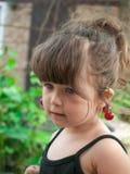 Pares colgantes de la niña pequeña de cerezas en su oído Imagen de archivo
