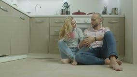 Pares com as bebidas quentes que sentam-se no assoalho da cozinha vídeos de arquivo