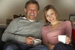 Pares com as canecas de café que prestam atenção à televisão Imagens de Stock