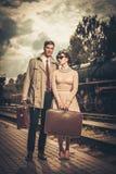 Pares com as malas de viagem na plataforma do estação de caminhos-de-ferro Fotografia de Stock Royalty Free