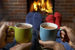 Pares com a bebida quente que relaxa pelo fogo Imagens de Stock Royalty Free