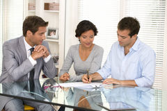 Pares com contrato home de assinatura do investimento do mediador imobiliário Foto de Stock Royalty Free