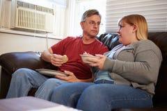 Pares com a dieta dos pobres que senta-se em Sofa Eating Meal Foto de Stock Royalty Free