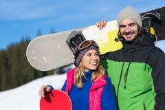 Pares com férias extremas de sorriso do esporte do homem e da mulher de Ski Resort Snow Winter Mountain do Snowboard Imagens de Stock Royalty Free
