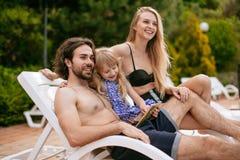 Pares com a filha em férias usando a tabuleta digital perto da piscina fotos de stock royalty free