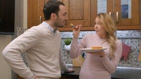 Pares com fome que comem o bolo delicioso, homem de alimentação da mulher, na cozinha em casa Fotos de Stock Royalty Free