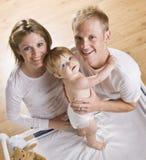Pares com o bebê na tabela em mudança Fotos de Stock Royalty Free