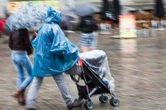 Pares com o buggy de bebê na chuva pesada foto de stock