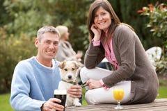 Pares com o cão de animal de estimação que aprecia ao ar livre a bebida no Pub imagens de stock