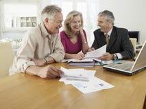 Pares com o conselheiro financeiro na tabela Foto de Stock Royalty Free