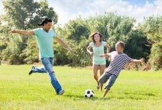Pares com o filho que joga com bola de futebol fotografia de stock