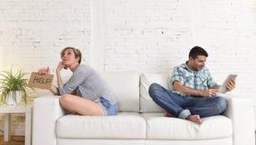 Pares com o marido feliz que usa o Internet app na almofada digital da tabuleta que ignora a esposa furada e triste imagens de stock