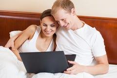 Pares com o portátil na cama Imagens de Stock