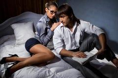 Pares com o portátil que encontra-se na cama Imagem de Stock Royalty Free