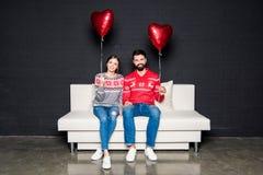 Pares com os balões vermelhos dos corações Fotografia de Stock Royalty Free