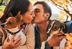 Pares com os cães que fazem o selfie ao beijar no parque do outono foto de stock royalty free