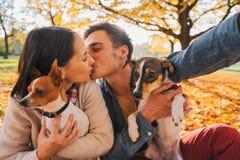 Pares com os cães que fazem o selfie ao beijar no parque do outono fotos de stock
