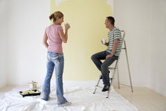Pares com os copos de café pela parede pintada Fotografia de Stock Royalty Free