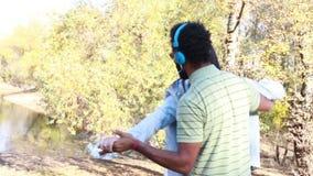 Pares com os fones de ouvido que escutam a música e que têm o divertimento pelo lago vídeos de arquivo