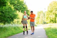 Pares com os patins de rolo que montam no parque do verão imagem de stock royalty free